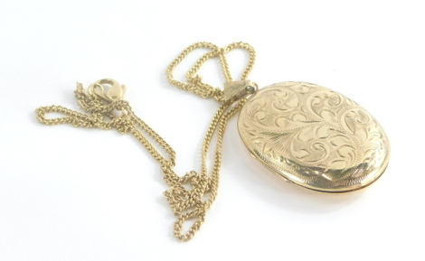A 9ct gold locket pendant and chain, the oval locket with floral scroll engraving, and single loop pendant opening to reveal two photograph section, on a yellow metal longuard chain with large clip clasp stamped 9ct, the pendant 5.5cm high, the chain 54cm