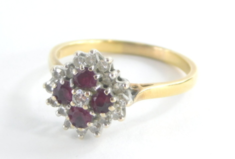 An 18ct gold ruby and diamond cluster ring, the central floral cluster set with four oval cut rubies and central tiny diamond, surrounded by twelve tiny diamonds each in claw setting on a raised basket setting with pierced shoulders, yellow metal stamped