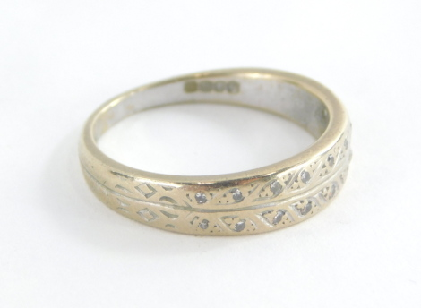 An 18ct white gold diamond set half hoop eternity ring, with tiny diamond set leaf design, ring size Q½, 5.1g all in.