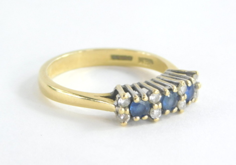 An 18ct gold sapphire and diamond set dress ring, set with three oval cut sapphires and six round brilliant cut diamonds, each in a raised platinum claw setting with pierced shoulders on a 18ct gold band, ring size P, 4.1g all in, boxed.