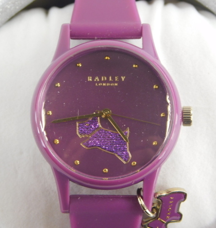 A Radley London ladies wristwatch, on purple plastic strap, with dial depicting Radley dog in glitter finish, in a silver cylindrical gift box and outer box.