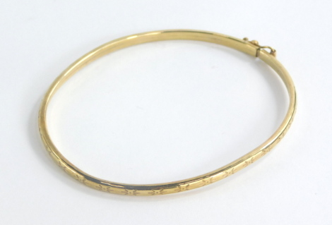 A silver hinged bangle, with star etched design, and safety clasp, yellow metal unmarked, 6cm diameter, 3.2g all in, boxed.