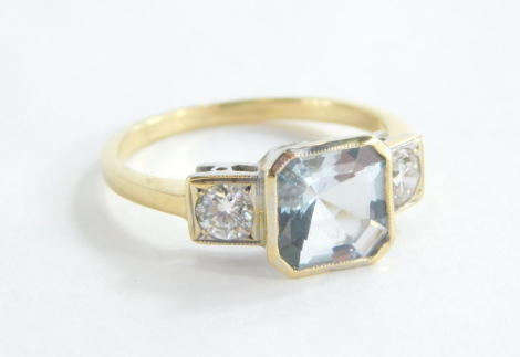 An aquamarine and diamond set dress ring, the square cut aquamarine in a rub over gold setting, with two round brilliant cut diamond shoulders each approx. 0.15ct, in platinum on a yellow metal band unmarked, believed to be 18ct, ring size N½, 3.7g all in