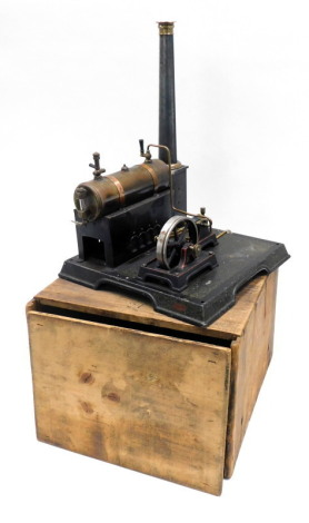 An early 20thC tin plate static engine, modelled with a brass and copper cylinder, ebonised and brass fittings, on a rectangular base with original pine box, in the manner of Marklin, 28cm wide.
