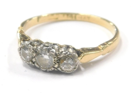 A diamond three stone dress ring, with three illusion set round brilliant cut diamonds, approx 0.15ct and two 0.10ct, in a platinum claw setting, with pierced design shoulders on a yellow metal band, stamped 18ct plat, ring size M½, 2.1g all in.