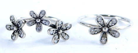 Two Pandora silver dress rings, one silver cluster ring, set with white crystals, ring size K, and a three group cluster floral ring, ring size K, 3.9g all in. (2, with one box)