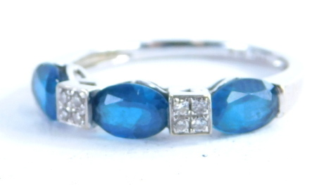 A 9ct white gold dress ring, set with three oval pale blue topaz and four tiny diamonds, on a plain band, ring size L½, 1.8g all in.