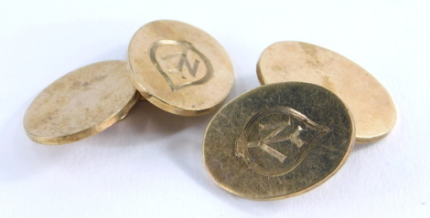 A pair of 9ct gold cufflinks, each with oval shield bearing the engraved initials NY, 12.6g all in.