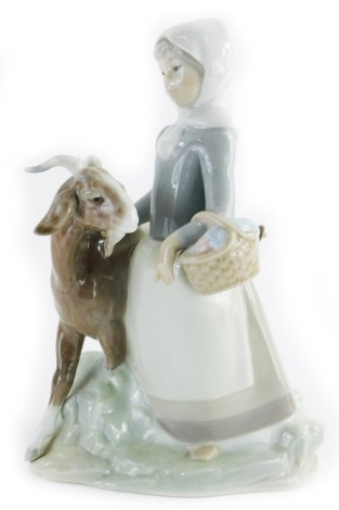 A Lladro porcelain figure group of a young girl with goat, 24cm high.