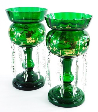 A pair of Victorian green glass table lustres, with gilt highlights, and various drops, 33cm high.