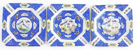 A set of three enamel hand painted ash trays, decorated with bird's, deer, flowers, etc., 10cm wide.