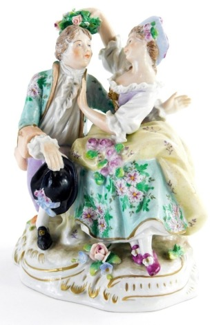 A 19thC Sitzendorf porcelain figure group, of a lady and gentleman, with gilt highlights, 16cm high.
