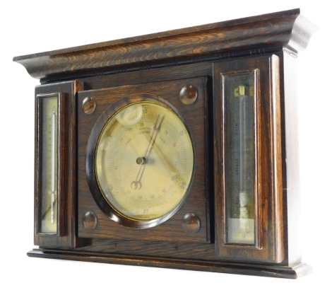 An early 20thC oak cased wall barometer, the central brass dial flanked by a mercury farenheit and centigrade measure, and a weather gauge, 31cm high, 46cm wide.