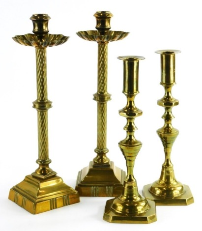 A pair of 19thC brass candlesticks, with a flare shaped drip tray, twisted stems, on square pedestal bases, 33cm high, and another pair of brass candlesticks.
