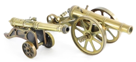 Two 19thC brass table cannons, the largest of plain form, 17cm long, the other decorated with motifs, star, etc., 21cm long. (2)
