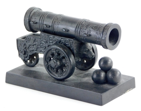 A miniature Russian cast iron model of a 16thC tsar cannon, the canon profusely decorated with four canon balls, on a square base, 12cm long.