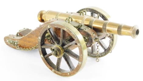 A model of an early 20thC cannon, in brass with a treen body, 36cm long.