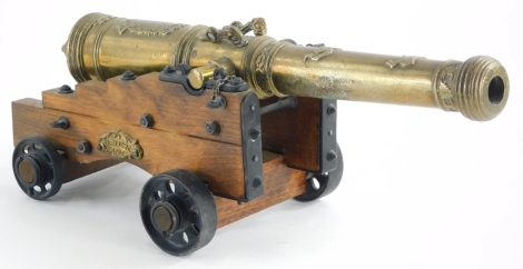 A reproduction brass table cannon of a Spanish El Tigre 1797 cannon, the body of the cannon cast with fish, armorial crest, design of scrolls, with a treen and cast metal frame, etc., 34cm long.