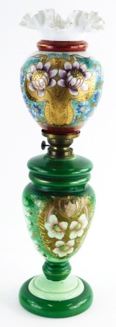 A Victorian opaque glass oil lamp, decorated with an arrangement of flowers, leaves, etc., 55cm high.