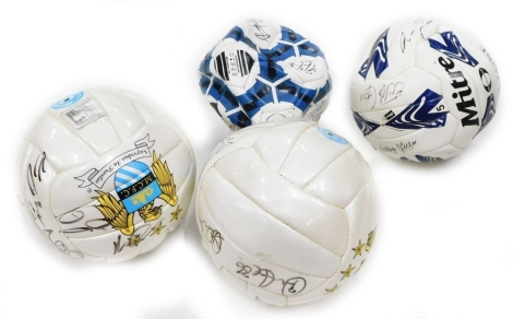 Two Manchester City signed footballs, and two others.