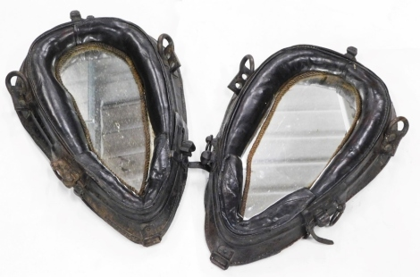A pair of late 19th/early 20thC brown leather horse collars, each with metal mounts, converted into wall mirrors.
